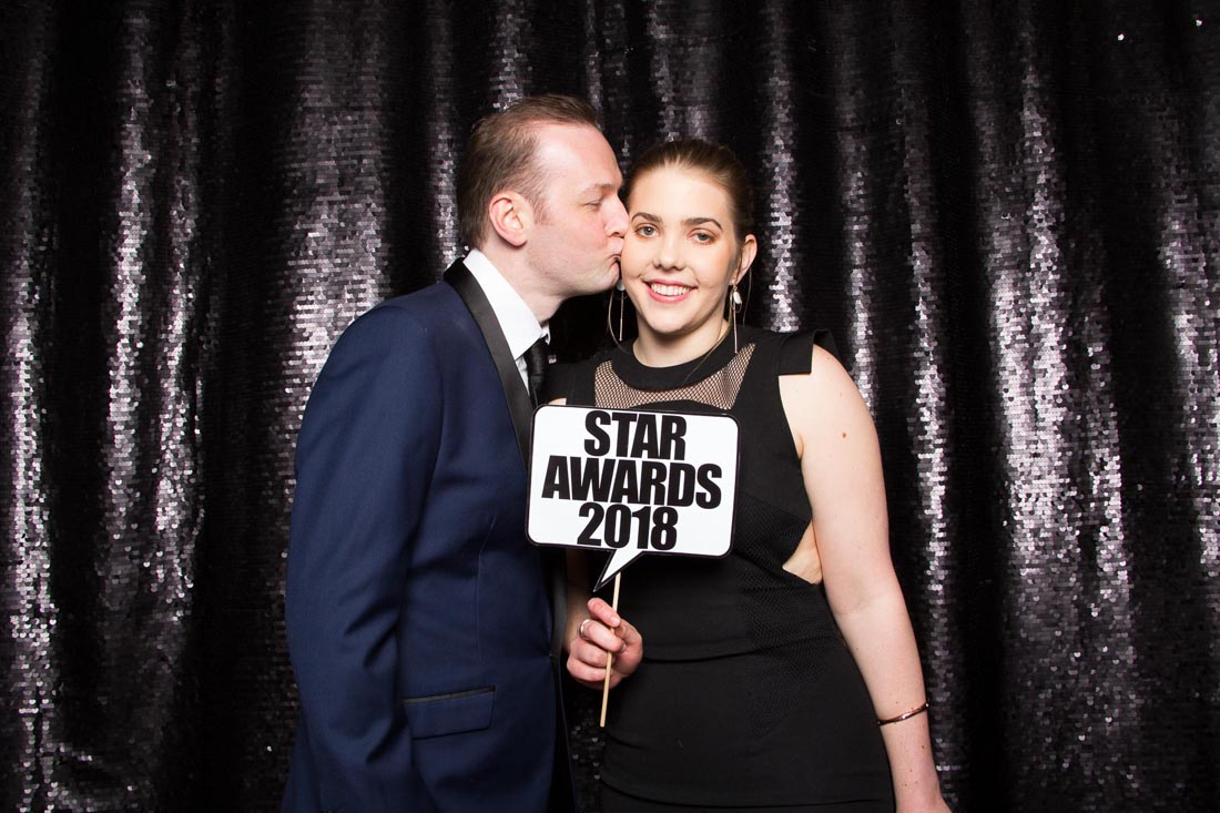 Couple with photo booth prop in front of a black sequin wall