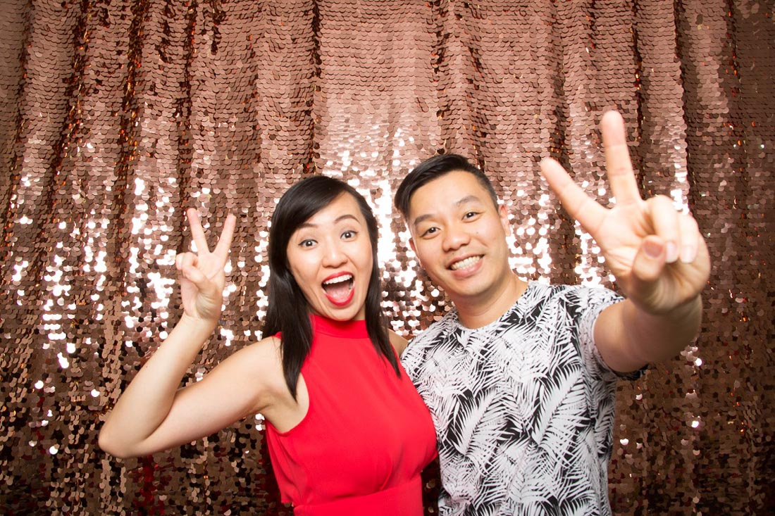 Couple holding their hands up in a peace sign in front of a rose sequin wall
