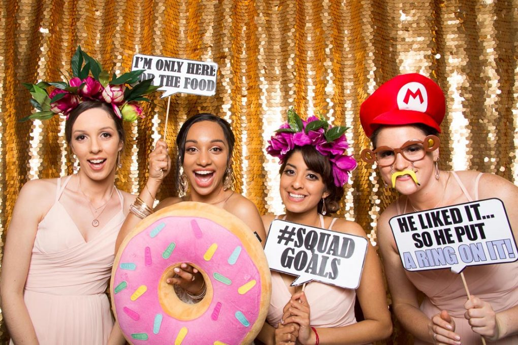 Friends in front of a golden sequin backdrop holding photo booth props