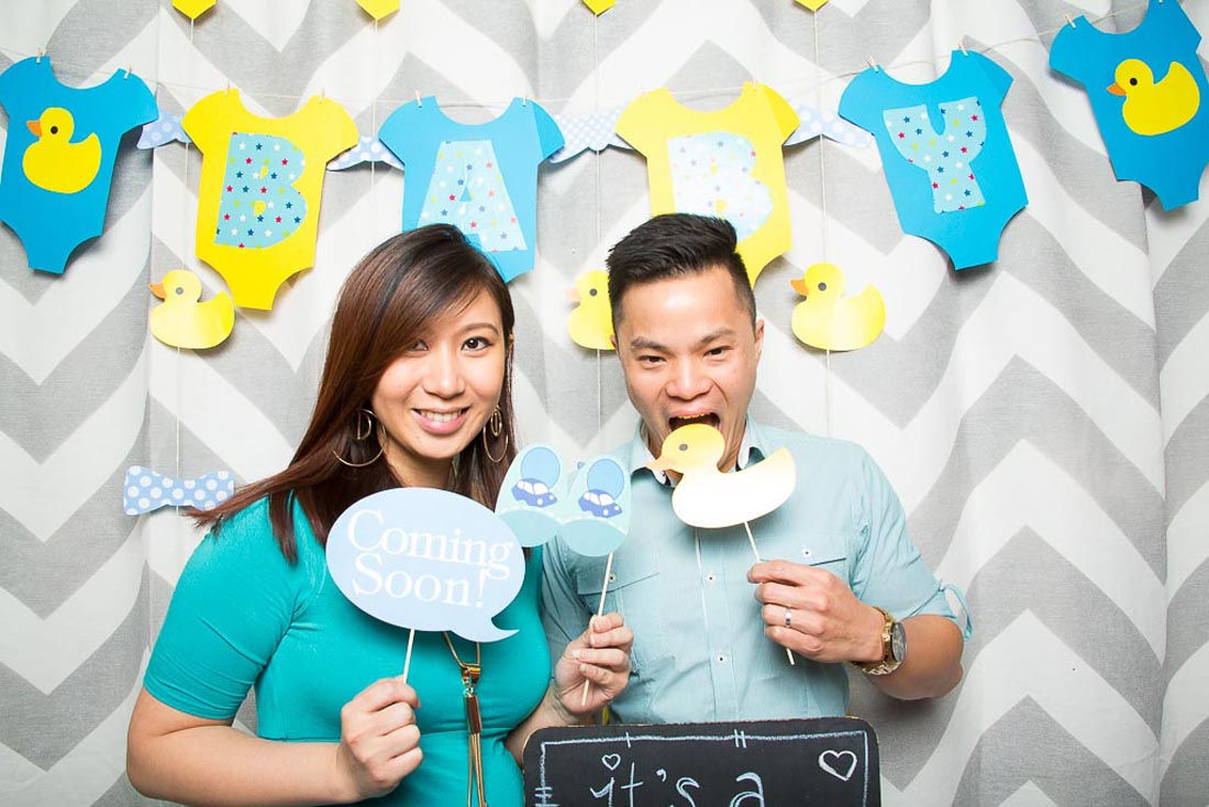 Couple holding baby photo booth props