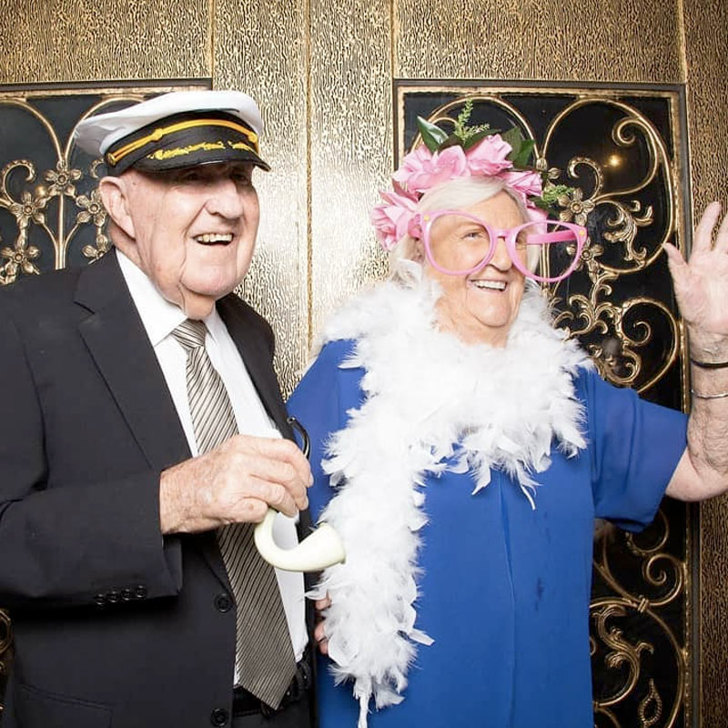 Elderly couple in dress up costumes at a photo booth