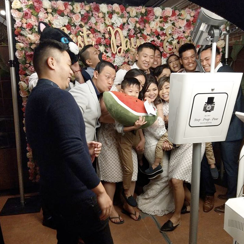 Big family in front of a photo booth with a flower wall backdrop