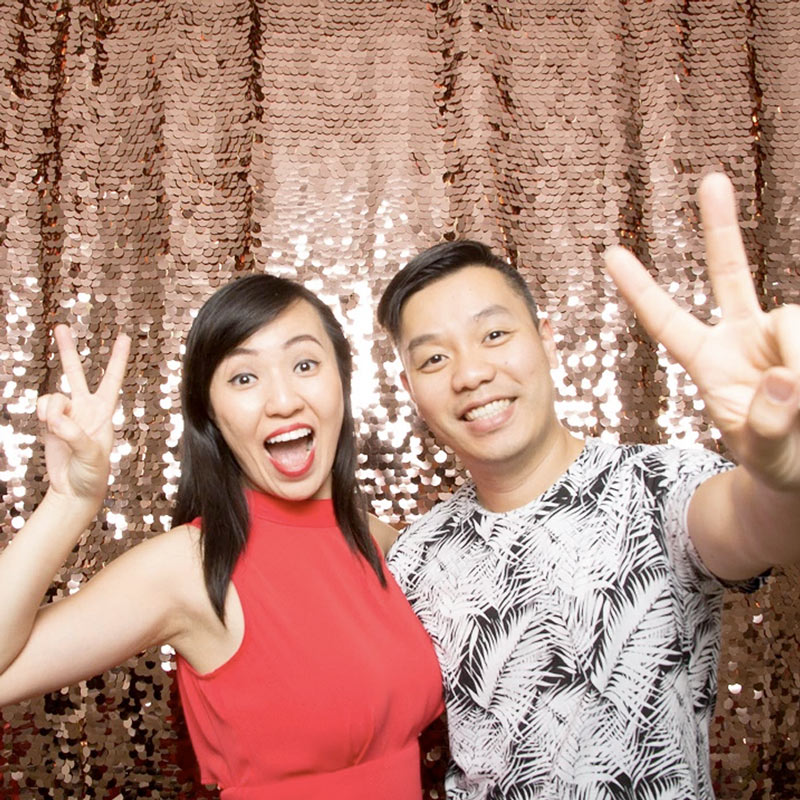 Man and woman posing in front of a sequin backdrop in front of a photo booth