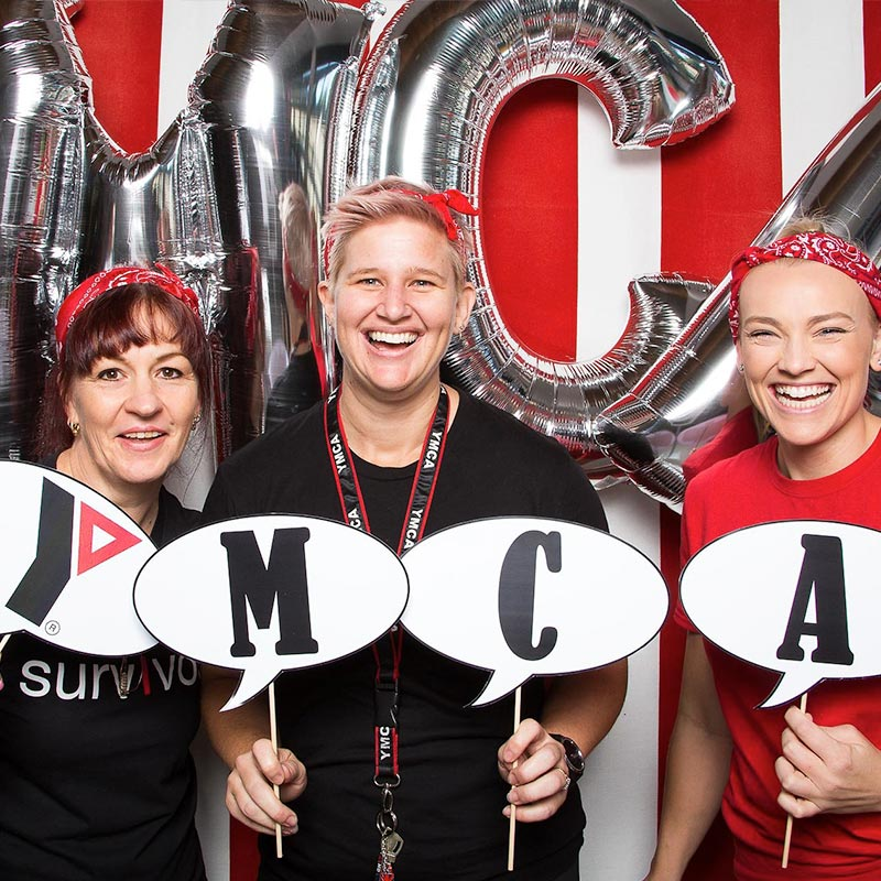 Women posing with YMCA sign in front of a red backdrop