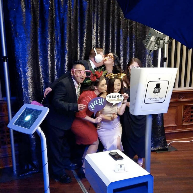 Group at a photo booth holding silly props