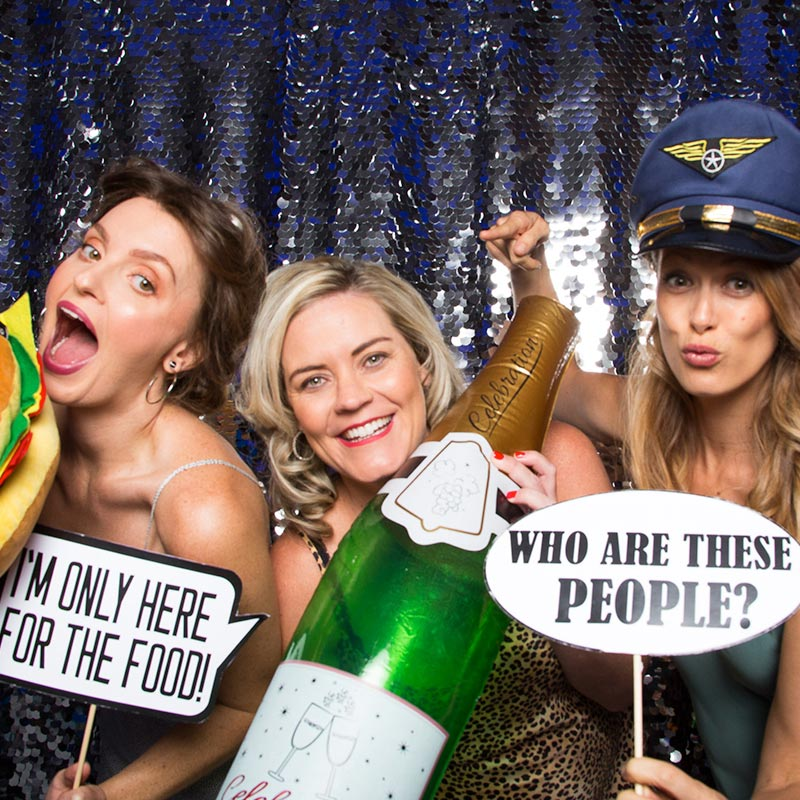 Three girls posing with funny props at a photo booth hire event