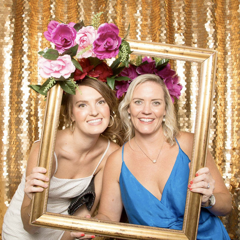 Two women holding a picture frame in front of a gold sequin wall