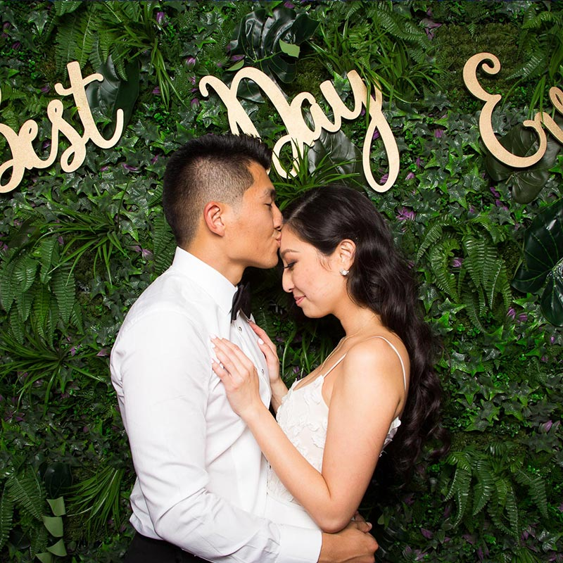 Man and woman kissing in front of a plant wall backdrop