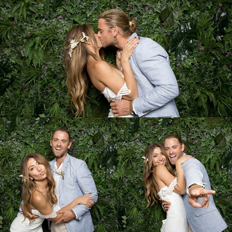 Couple at a photo booth with a plant wall backdrop