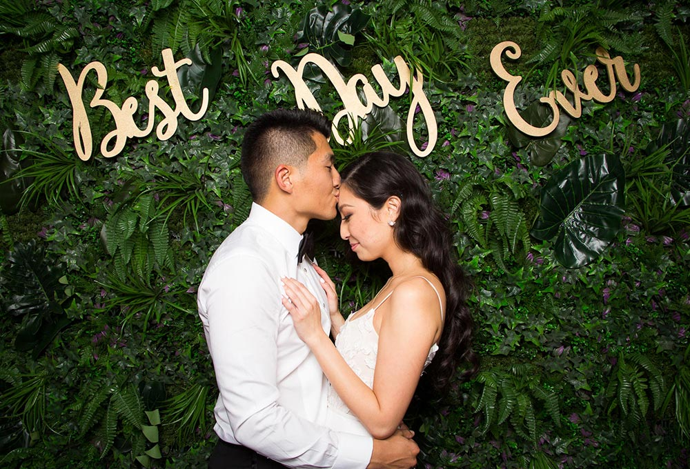 Couple kissing with a plant background and photo booth hire event