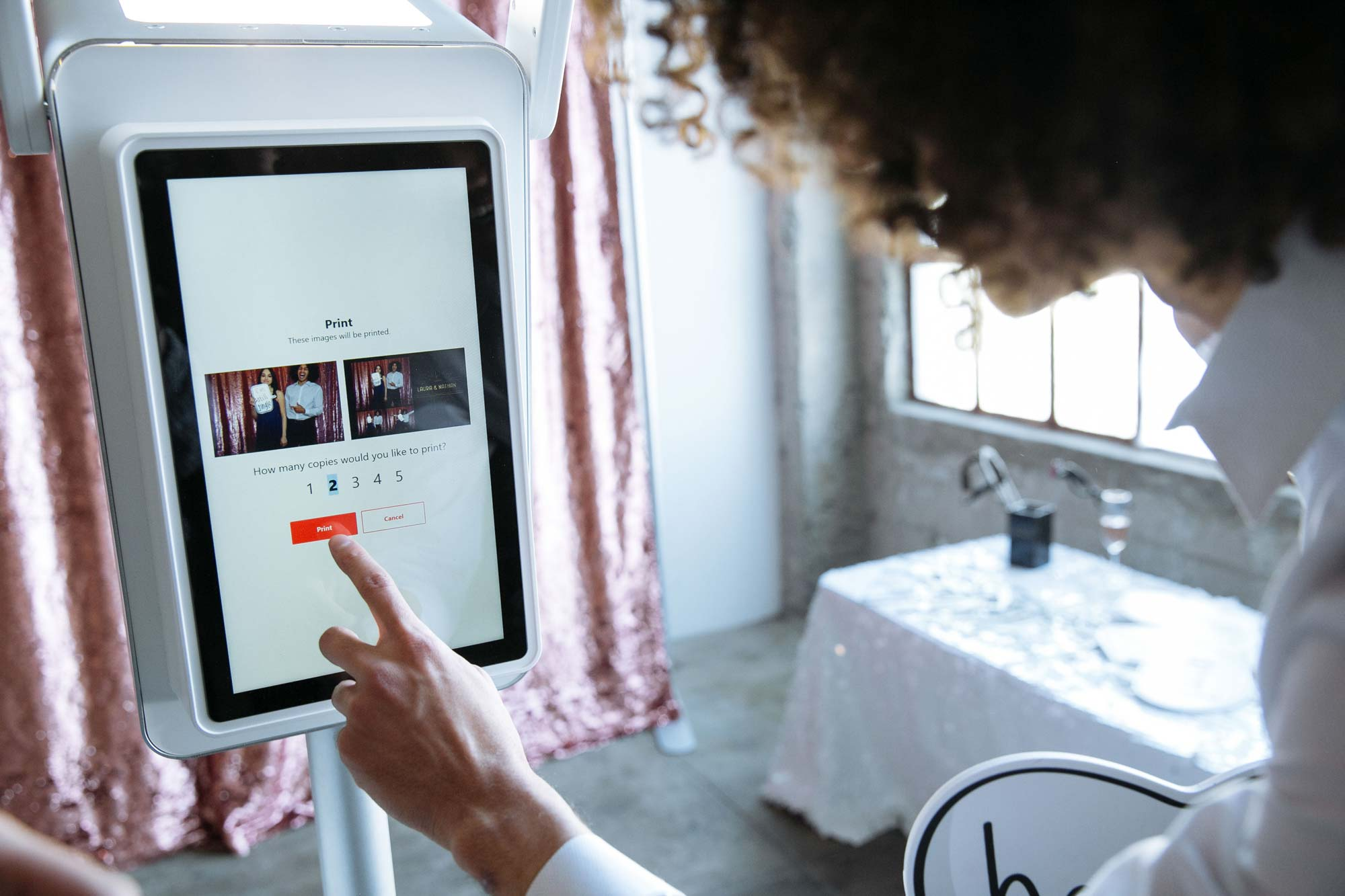Woman selecting her photo to print on a photo booth