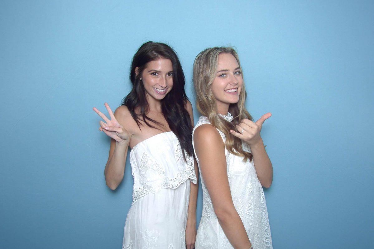 Two women posing in front of a blue backdrop