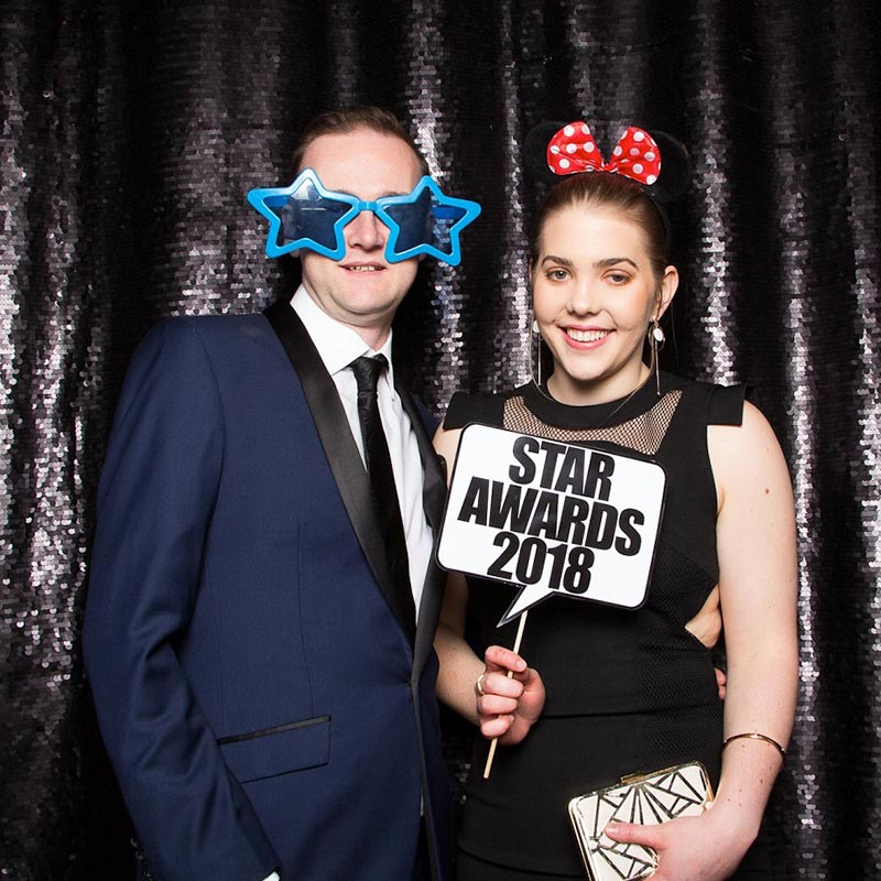 Man and woman posing with props in front of a black sequin backdrop