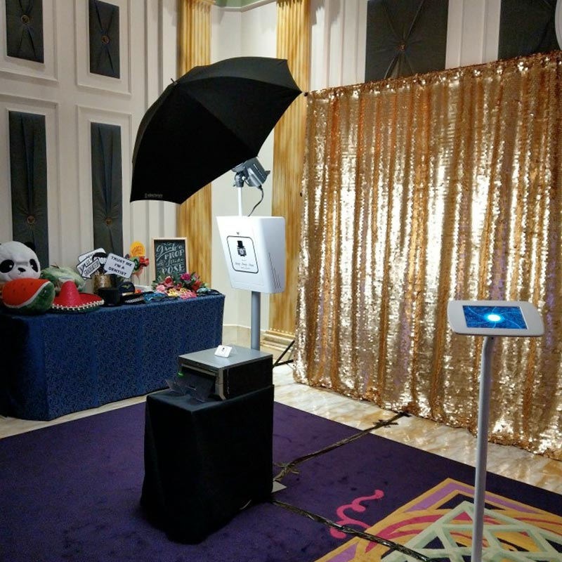 click.click photo booth set up including a gold sequin backdrop