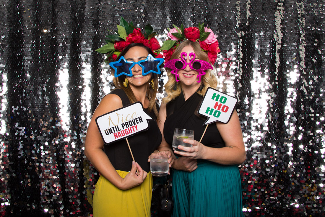 Two women posing in front of a silver backdrop holding photo booth props