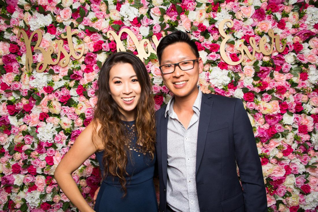 Couple standing and posing in front of a pink flower wall
