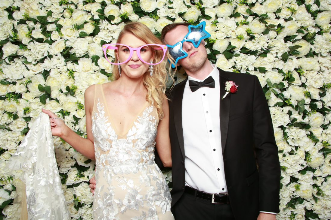 Bride and groom posing in front of a white flower wall