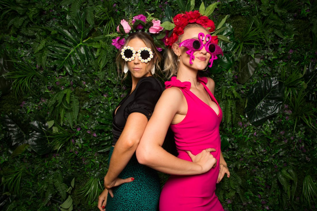 Two ladies posing in front of a Green Wall