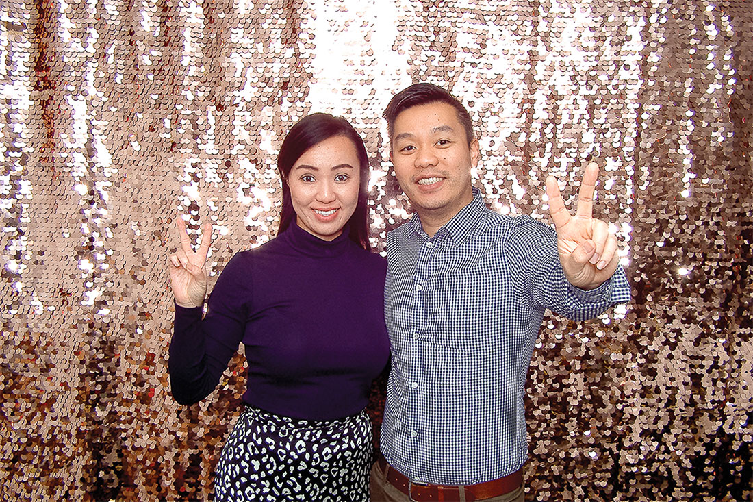 Man and woman posing in front of a photo booth